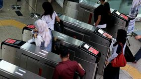 People going through the turnstile in the subway stock footage