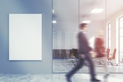Gray office lobby, meeting room, people. People in a gray office lobby with a concrete floor, loft windows and a glass wall. There is a large vertical poster and Stock Photography