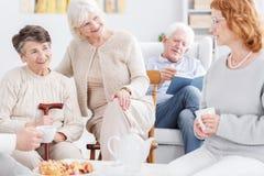 Older women having nice conversation. People in great moods at nursing home, three older women having a nice conversation while a senior men is reading book in Royalty Free Stock Photo