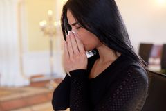 Close up of crying woman at funeral in church Stock Photo