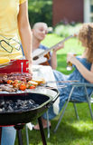 People grilling, playing guitar and singing Royalty Free Stock Photos