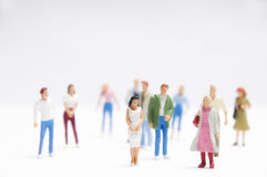 People group. Miniature figurines of people of various age and gender on white background Stock Images