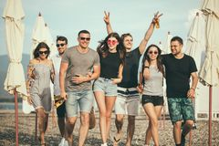 Holidays, vacation. group of friends having fun on beach, walking, drink beer, smiling and hugging stock photo