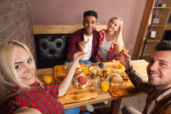 People Group Eating Fast Food Burgers Potato Sitting At Wooden Table In Cafe Taking Selfie Photo Stock Images