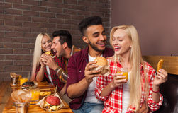 People Group Eating Fast Food Burgers Sitting At Wooden Table In Cafe. Friends Meeting Communication Stock Image