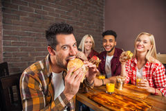 People Group Eating Fast Food Burgers Sitting At Wooden Table In Cafe Stock Photos