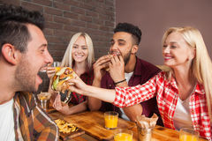 People Group Eating Fast Food Burgers Sitting At Wooden Table In Cafe. Friends Meeting Communication Royalty Free Stock Photo
