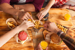 People Group Friends Hands Eating Fast Food Burgers Potato Drinking Orange Juice. Cafe Wooden Table Top Angle View Royalty Free Stock Images
