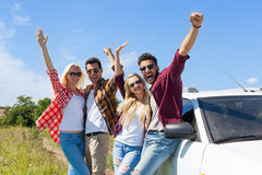 People group outdoor countryside excited raise arms friends smile. Holding hands up near car summer day trip Stock Photos