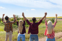 People group outdoor countryside excited raise arms rear back view friends holding hands up. Summer day Stock Photo