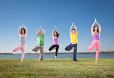 People in group practice Yoga asana on lakeside. stock photo