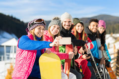 People Group With Snowboard And Ski Resort Snow Winter Mountain Cheerful Taking Selfie Photo. Friends Hands Having Fun royalty free stock photography