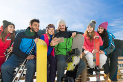 People Group With Snowboard And Ski Resort Snow Winter Mountain Cheerful Watching Video. On Cell Smart Phone Stock Photography