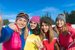 People Group With Snowboard And Ski Resort Snow Winter Mountain Girls Cheerful Taking Selfie Photo. Friends Hands Having Fun royalty free stock image