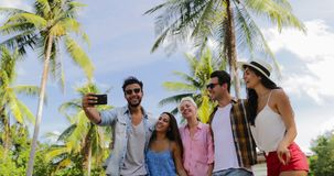 People Group Take Selfie Photo On Cell Smart Phone Outdoors Under Palm Trees, Happy Smiling Mix Race Man And Woman. Communication Slow Motion 60 stock footage