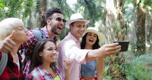 People Group Taking Selfie Photo On Cell Smart Phone On Hike, Men And Woman Trekking In Tropical Palm Tree Forest. Slow Motion 60 stock video footage