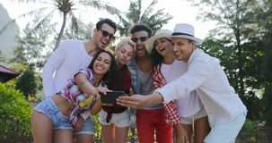 People Group Taking Selfie Photo On Cell Smart Phones Happy Men And Women Over Tropical Palm Trees. Slow Motion 60 stock video footage