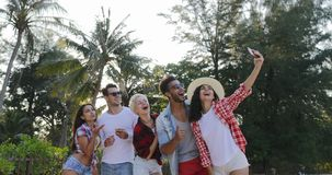 People Group Taking Selfie Photo On Cell Smart Phones Talking Happy Men And Women Over Tropical Palm Trees. Slow Motion 60 stock video