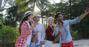 People Group Taking Selfie Photo On Cell Smart Phones Talking Happy Men And Women Over Tropical Palm Trees stock video footage