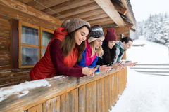 People Group Using Smart Phone Messaging Internet Wooden Country House Winter Snow Mountain Resort Cottage Stock Image