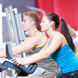 People in the gym doing cardio cycling training. Group of two people in the gym, exercising their legs doing cardio cycling training Stock Photo