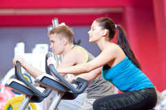 People in the gym doing cardio cycling training. Group of two people in the gym, exercising their legs doing cardio cycling training Stock Photos