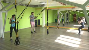 People in the gym are engaged on the TRX loops and perform an extension exercise on the triceps, muscle strengthening