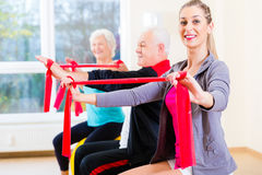 People at gym exercise with stretch band Stock Photography
