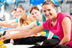 People in gym warming up stretching Stock Images