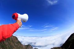 People hand hold loudspeaker to blue sky on mountain Royalty Free Stock Images