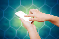 People hand hold and touch screen smart phone on soccer goal net. Background Stock Photos