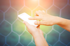 People hand hold and touch screen smart phone on soccer goal net. Background Stock Image