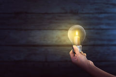 People hand holding bright candle inside light bulb. On the dark room Royalty Free Stock Photography