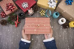 Hand holding Christmas presents gift  among set on wooden table background. Stock Image