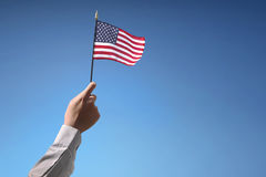 People hand holding the flag of USA celebrating 4th of July Royalty Free Stock Photo