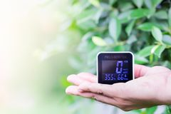 People hand holding PM 2.5 detector checking dust on blurred green leaf. royalty free stock image