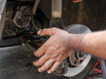 People hand maintenance fixing disc brake car. Royalty Free Stock Images
