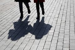 Silhouettes and shadows of two women walking down the street royalty free stock photo