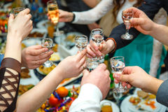 People hands Clinking glasses with vodka and wine Royalty Free Stock Photos