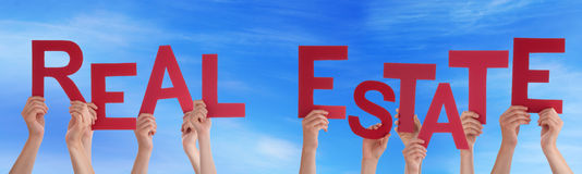 People Hands Holding Red Word Real Estate Blue Sky. Many Caucasian People And Hands Holding Red Letters Or Characters Building The English Word Real Estate On Royalty Free Stock Photos