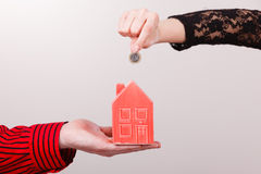 People hands with little house and silver coin. Stock Photo