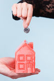 People hands with little house and silver coin. Royalty Free Stock Photo