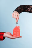 People hands with little house and silver coin. Stock Images