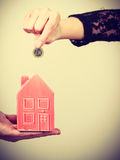 People hands with little house and silver coin. Stock Photos