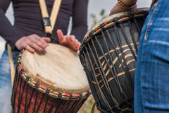 People hands playing music at djembe drums stock image