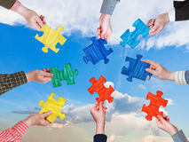 People hands with puzzle pieces with afternoon sky Royalty Free Stock Image