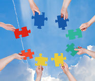 People hands with puzzle pieces with blue sky Royalty Free Stock Photo