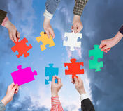 People hands with puzzle pieces with grey clouds Royalty Free Stock Images