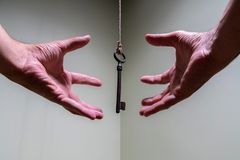 People hands reaching for vintage key hanging on a string. Business success freedom concept concept for aspirations, achievement. And incentive stock photography