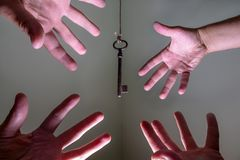 People hands reaching for vintage key hanging on a string. Business success freedom concept concept for aspirations, achievement stock photos